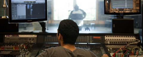 A student records a classmate in an audio production class.