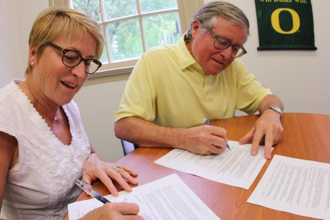 Mary Ann and Niles Hanson sign their gift agreement.
