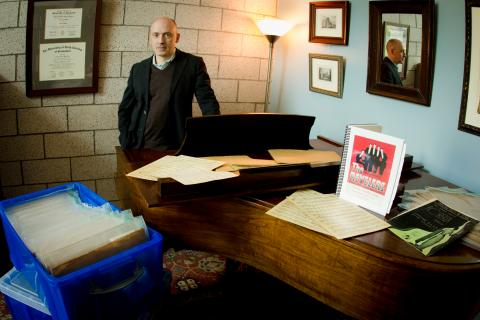 """Assistant professor of voice Craig Phillips poses with long lost musical scores from the 1930s vocal quartet """"The Revelers."""" (Photo credit: Erin Zysett)"""