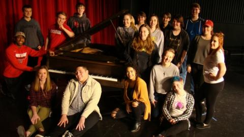 Members of the North Eugene High School choir pose with one of the baby grand pianos donated by the University of Oregon School of Music and Dance.