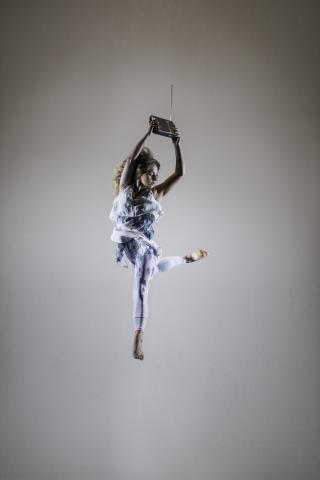 """Dancer Olivia Oxholm strikes a pose with a radio, used as a prop for the show """"Tesla: Light, Sound, Color."""" (photo credit: Jennifer James-Long / Studio Sura)"""
