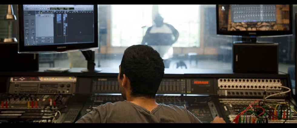 A student runs the mixing board during a recording session in Aasen-Hull Hall